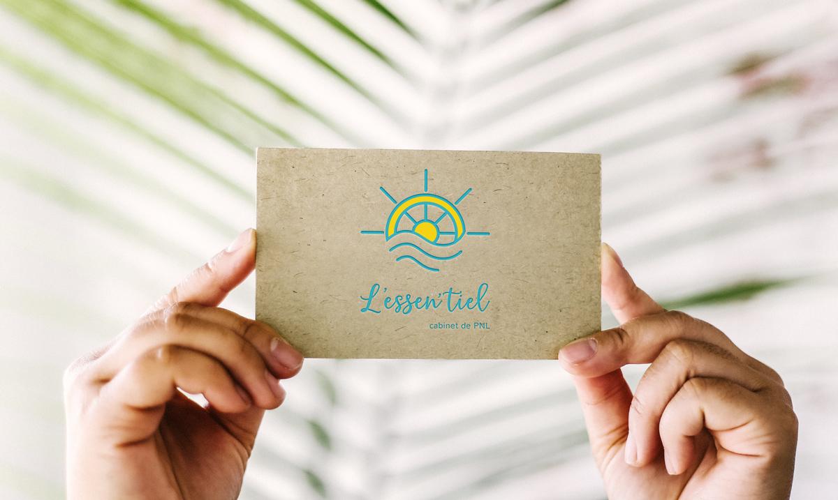 Logo d'un gouvernail sur une carte de visite tenue entre deux mains